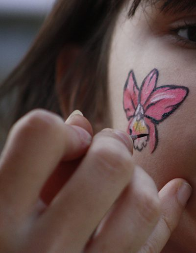Painting an orchid on a child's cheek
